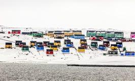 Bunte Inuithäuser auf Schneehügel, Aasiaat-Stadt stockbild
