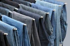 Bunte Jeans, die an den Aufhängern hängen Lizenzfreies Stockfoto