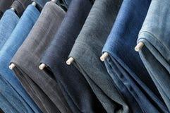 Bunte Jeans, die an den Aufhängern hängen Lizenzfreie Stockbilder