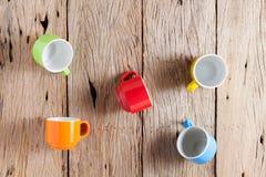 Bunte Kaffeetassen auf altem hölzernem Hintergrund Stockbild