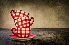 Bunte Kaffeetassen auf dem Tisch in der Weinleseart Stockbilder