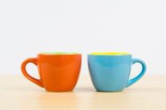 Bunte Kaffeetassen auf hölzerner Brettnahaufnahme Lizenzfreie Stockfotos