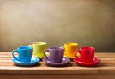 Bunte Kaffeetassen auf hölzerner Tabelle Stockbilder