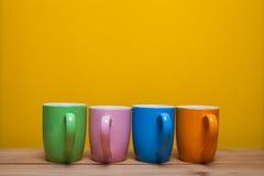 Bunte Kaffeetassen auf Holztisch über gelbem Hintergrund Lizenzfreie Stockfotos