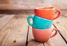 Bunte Kaffeetassen auf Holztisch über Schmutzhintergrund Lizenzfreie Stockfotos