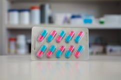 Bunte Kapselpillen mit Unschärferegalen der Droge Stockfotos