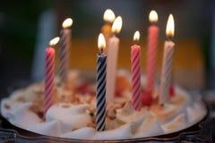 Bunte Kerzen auf Geburtstagkuchen Stockbilder