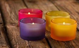 Bunte Kerzen auf rustikalem hölzernem Hintergrund Stockfotografie