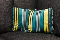 Bunte Kissen auf grauer Couch Stockfotografie