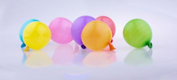 Bunte kleine Ballone auf einem weißen Hintergrund Stockfoto