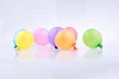 Bunte kleine Ballone auf einem weißen Hintergrund Lizenzfreie Stockfotografie