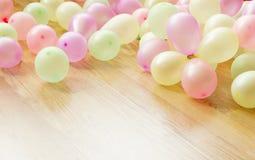 Bunte kleine Ballone, die auf Bretterboden liegen Stockfotos