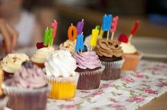 Bunte kleine Kuchen mit Sahne, Beeren und Kerzen Lizenzfreies Stockfoto