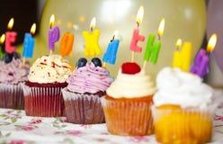 Bunte kleine Kuchen mit Sahne und frische Beeren mit brennenden Kerzen Lizenzfreie Stockbilder