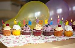 Bunte kleine Kuchen mit Sahne und neue Beeren und Kerzen Lizenzfreies Stockbild