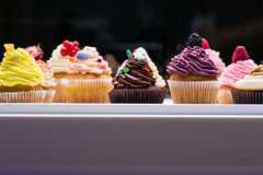 Bunte kleine Kuchen mit verschiedenen Geschmäcken Kleine schöne Kuchen auf weiße Tischplatte Lizenzfreie Stockbilder