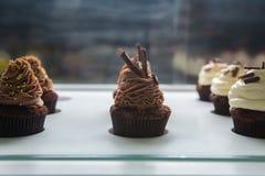 Bunte kleine Kuchen mit verschiedenen Geschmäcken Kleine schöne Kuchen auf weiße Tischplatte Lizenzfreies Stockbild