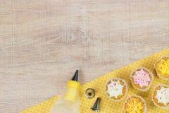 Bunte kleine Kuchen und Backenwerkzeuge auf einem Holztischhintergrund stockfoto