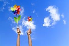 Bunte kleine Windmühlen in den Händen Lizenzfreies Stockfoto