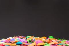 Bunte Konfettis auf schwarzem Schiefer als Schablone für Feier Stockbild
