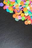Bunte Konfettis auf schwarzem Schiefer als Schablone für Feier Stockfoto