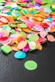 Bunte Konfettis auf schwarzem Schiefer als Schablone für Feier Stockfotografie