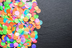 Bunte Konfettis auf schwarzem Schiefer als Schablone für Feier Lizenzfreies Stockbild