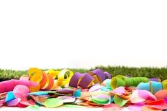 Bunte Konfettis und Ausläufer auf Gras vor Hintergrund Lizenzfreies Stockbild