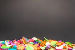 Bunte Konfettis vor schwarzem Hintergrund als Schablone Stockfoto