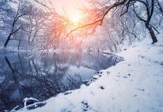 Bunte Landschaft mit schneebedeckten Bäumen, schöner gefrorener Fluss an Stockfotografie