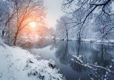 Bunte Landschaft mit schneebedeckten Bäumen, schöner gefrorener Fluss an Lizenzfreies Stockbild