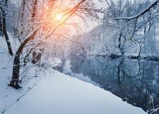 Bunte Landschaft mit schneebedeckten Bäumen, schöner gefrorener Fluss an Stockfotos