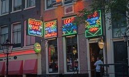 Bunte Leuchtreklamen, die roten Lichtstrahl in Stadt ` s Rotlichtviertel fördern Lizenzfreie Stockfotografie
