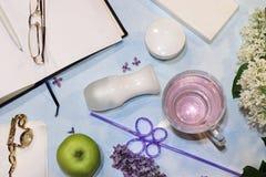 Bunte lila Niederlassungen auf einem blauen Hintergrund, Hautpflege sahnt, desodorierendes Mittel, offenes Notizbuch und Smartpho lizenzfreie stockfotografie