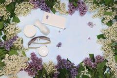 Bunte lila Niederlassungen auf einem blauen Hintergrund mit Saft, Hautpflege sahnt, desodorierendes Mittel und Gl?ser, flache Lag stockbilder