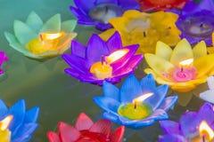 Bunte Lotosblume mit brennenden Kerzen schwimmen auf das Wasser, um den Buddha mit anzubeten beten Segen bei bei Wat Rong Suea Stockfotos
