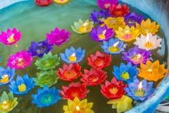 Bunte Lotosblume mit brennenden Kerzen schwimmen auf das Wasser, um den Buddha mit anzubeten beten Segen bei bei Wat Rong Suea Stockfoto