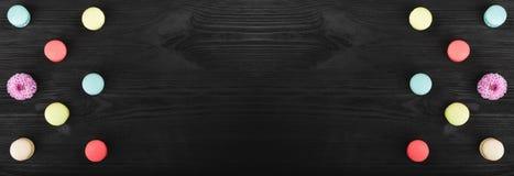 Bunte macarons vereinbarten symmetrisch, Spiegeleffekt auf Holztisch mit Kopienraum lizenzfreie stockfotografie