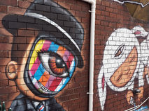 Bunte Mann-Graffiti gemalt auf Backsteinmauer Stockbild