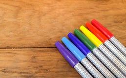 Bunte Markierungs-Stifte in der Regenbogen-Bestellung auf Holztisch Stockbild