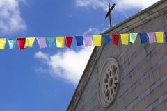 Bunte Markierungsfahnen in der Luft, eine Kirche im backgro lizenzfreie stockbilder