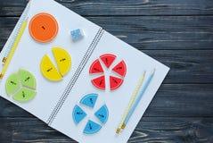 Bunte Mathebrüche auf dem Arbeitsbuch interessantes Mathe für Kinder Bildung, zurück zu Schule stockfotografie