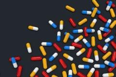 Bunte Medizinkapseln auf dem schwarzen Hintergrund, horizontal stock abbildung