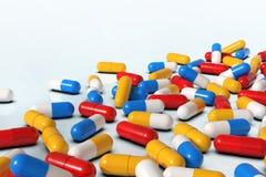 Bunte Medizinkapseln auf weißem Hintergrund stock abbildung