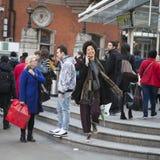 Bunte Menge, die an einem Fußgängerübergang, beabsichtigend, die Straße zu kreuzen wartet Stockfotos