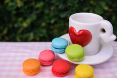 Bunte Mini-macarons mit Liebesbecher Stockfotografie