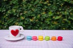 Bunte Mini-macarons mit Liebesbecher Lizenzfreie Stockfotografie