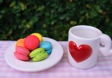 Bunte Mini-macarons mit Liebesbecher Lizenzfreies Stockbild