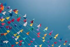 Bunte mit dem Kopfe stoßende Flaggen auf blauem Himmel auf Hintergrund lizenzfreie stockbilder