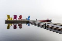 Bunte Muskoka-Stühle auf einem Dock Stockbild